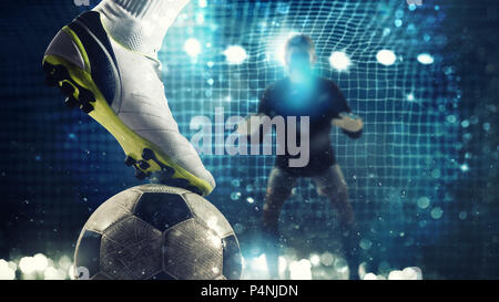 Close up of a soccer striker ready to kicks the ball in the football goal - Stock Photo