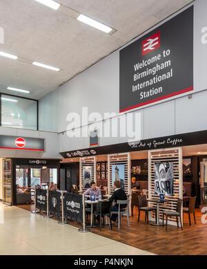 Customers in Caffè Ritazza, under s sign saying Welcome to Birmingham International Station. Birmingham Airport, England, UK - Stock Photo