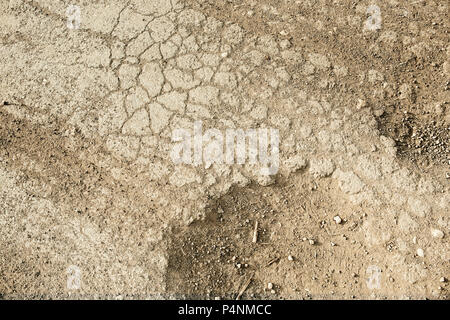 Wheel trace on road .Traces on soil of tractor, excavator, car, automotive tire tracks on muddy trail. Background, texture - Stock Photo