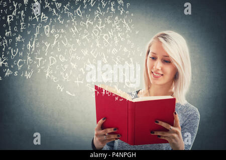 Beautiful blonde girl read and flying alphabet letters escape from the red book. The magic of lecture. Young school teacher studying, educational and  - Stock Photo