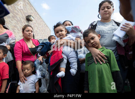 Immigrant mothers, wearing electronic monitoring devices, and their young children captured coming across the United States-Mexico border in Texas are released at a bus station in McAllen. The families will travel to stay with family members in the U.S. while awaiting deportation or asylum hearings. - Stock Photo