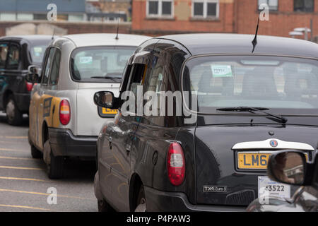 a row of London black cabs taxis waiting for fares. - Stock Photo