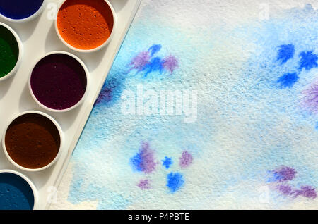 A new set of watercolors lies on a sheet of paper, which shows an abstract watercolor drawing in the form of blue strokes. The concept of amateur pain - Stock Photo