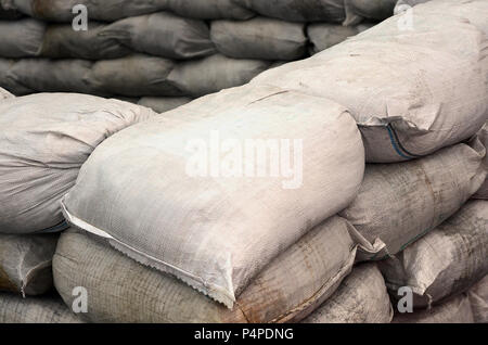 Background of many dirty sand bags for flood defense. Protective sandbag barricade for military use. Handsome tactical bunker . - Stock Photo