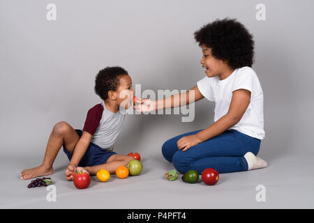 Young cute African siblings together against gray background - Stock Photo