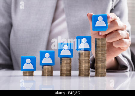 Businesswoman's Hand Placing Blue Cubic Block With Candidate Icon On Increasing Stacked Coins - Stock Photo