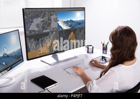 Rear View Of A Woman Working On 3D Landscape On Computer In Office - Stock Photo