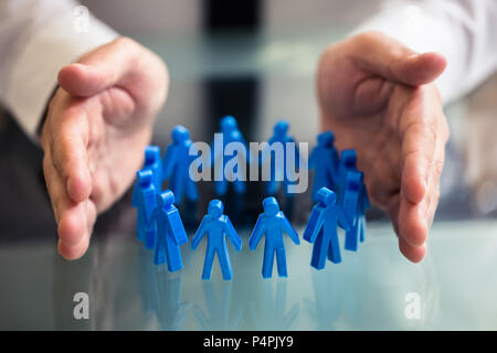 Close-up Of A Businessperson's Hand Protecting Blue Human Figures Forming Circle - Stock Photo