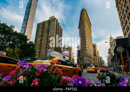 Summer 2015 Flatiron Building at Fifth Avenue and taxi cabs, New York USA - Stock Photo