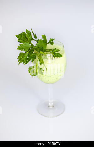 Parsnip, parsley cocktail, drink in a wine glass. Leaves as decoration.  Healthy food, slow life style. - Stock Photo