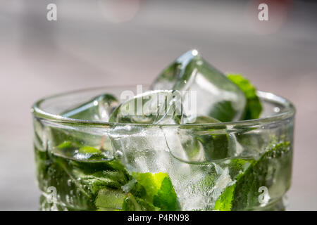 Twigs green mint in mojito with slices lime, ice cubes, straw, macro, texture, blur - Stock Photo