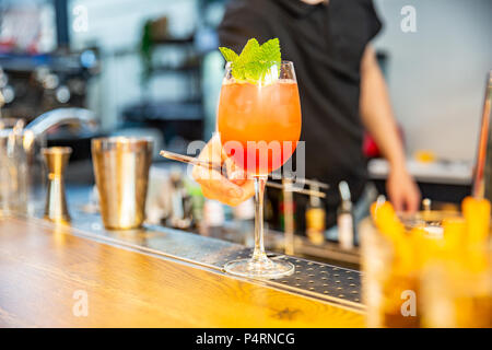 Bartender finished decorating his cocktail with mint - Stock Photo