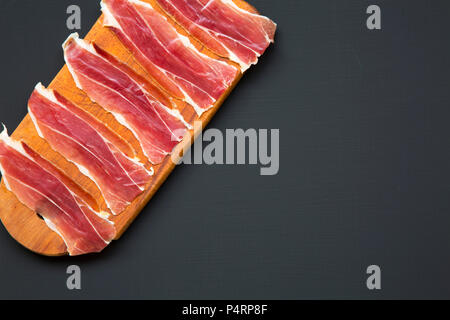 Sliced jamon Serrano or Iberico on cutting wooden board. Traditional spanish hamon on dark wooden background, top view. Copy space. - Stock Photo