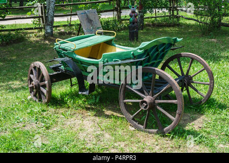 An old carriage for trips in a harness with a horse stands on the grass - Stock Photo