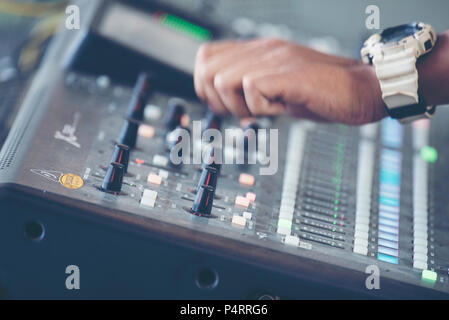 professional stage sound mixer closeup at sound engineer hand using audio mix slider working during concert performance - Stock Photo