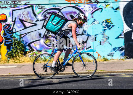 Deliveroo bicycle delivery rider struggling in the heat, riding past bright graffiti in Southend on Sea, Essex, UK. Cyclist take away food delivery - Stock Photo