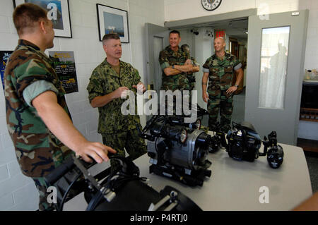 (August 5, 2010) Master Chief Petty Officer of the Navy (MCPON) Rick West meets with Sailors and tours the spaces of Combat Camera during his visit to Naval Station Norfolk. West is wearing the Navy Working Uniform Type III during the conformance test phase. - Stock Photo