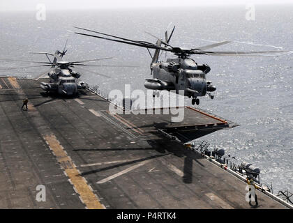 A U.S. Marine Corps CH-53E Super Stallion helicopter assigned to Helicopter Marine Medium Squadron (HMM) 165 takes off from the flight deck of USS Peleliu (LHA 5) with Marines aboard who will support flood relief in Pakistan Aug. 12, 2010, in the Arabian Sea. - Stock Photo