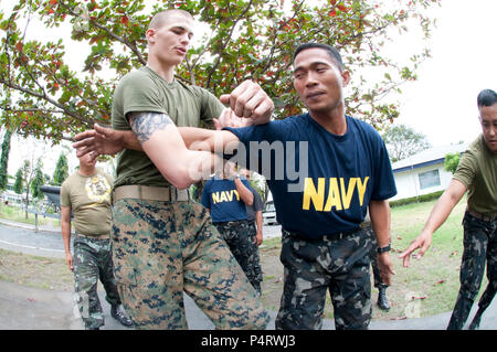 U.S. Marine Corps Lance Cpl. Kenneth Pollard, left, assigned to Fleet Anti-Terrorism Security Team (FAST) Pacific, teaches Filipino sailors and marines martial arts techniques during a professional development exchange at Naval Station Sangley Point, Philippines, Feb. 15, 2011. FAST was embarked aboard the U.S. 7th Fleet command ship USS Blue Ridge (LCC 19). (DoD - Stock Photo