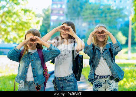 Three teenage girls. Summer in nature. Smile happily. In Stylish Denim Clothing. Hands gesture shows love. Concept kindness and positive. Emotions of happiness and friendship. Rest after school. - Stock Photo