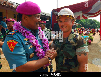 Indonesian Marine Corps Brig. Gen. Arif Suherman, left, the commander of Naval Base 3 Jakarta, shakes hands with U.S. Navy Builder 3rd Class Jermaine Takai, assigned to Amphibious Construction Battalion 1, at a ribbon cutting ceremony for an engineering civic action project in support of Cooperation Afloat Readiness and Training (CARAT) Indonesia 2011 at the Ciangsana Elementary School in Jakarta, Indonesia, May 30, 2011. CARAT is a series of bilateral exercises held annually in Southeast Asia to strengthen relationships and enhance force readiness. (DoD - Stock Photo