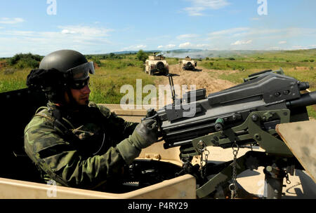 A member of the Slovak Republic 5th Special Forces Regiment conducts security with a U.S. 50-caliber heavy machine gun inside a HUMMV as other members of his team position their vehicles to do the same at the Military Training Center in Slovakia as part of a Partnership Development Program event. - Stock Photo