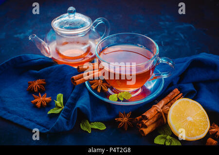 Black tea glass teacup, linen napkin, lemon slices, cinnamon, anise stars and mint leaves on a dark background. Dark food photography header with copy - Stock Photo