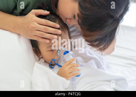 Asian baby girl breathing treatment with mother take care, at room hospital, close up health care kid concept sunny light background. - Stock Photo