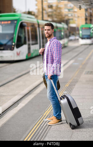 Young man waiting his train in urban subway station. Traveler wearing casual clothes. Lifestyle concept. - Stock Photo