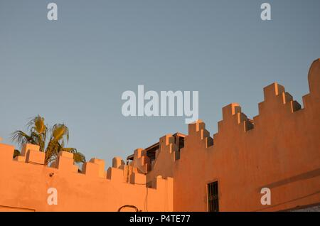 Oriental house facade during sunset in Marrakech Morocco, souk, palm trees, colors, sky, orange, ocher, architecture, Atlas mountains, markets - Stock Photo