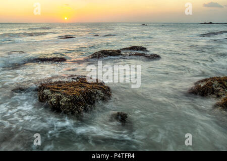 Long exposure shot of rocks covered with algae and sea weed not covered by sea during low tide, in sunset light. Koh Lanta, Thailand - Stock Photo