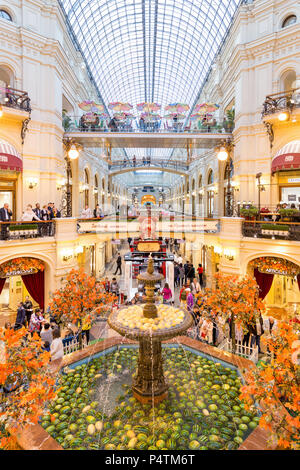 Moscow, Russia - September 16, 2017: Gum department store, the oldest shopping mall decorated by watermelons in fountain roundabout, people walking ar - Stock Photo