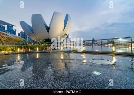 Beautiful blue hour with Singapore Art Science Museum as seen from Helix Bridge. The architecture is said to be a form reminiscent of a lotus flower. - Stock Photo
