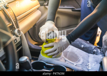 a man cleaning car interior by use foam chemical  and scrubbing machine. - Stock Photo