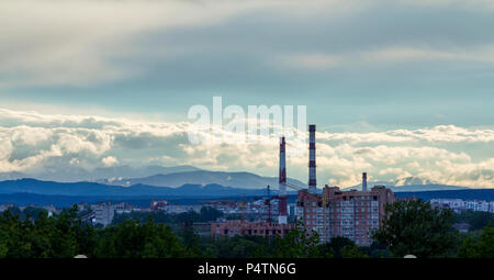 Wide panorama of modern urban building site of residential apartments quarter in city with green trees, working tower cranes, high pipe chimneys under - Stock Photo