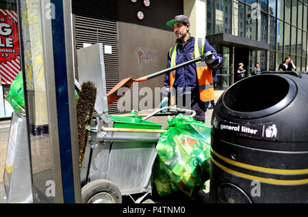 Street cleaner emptying rubbish bins in the Strand, central London, England, UK. - Stock Photo