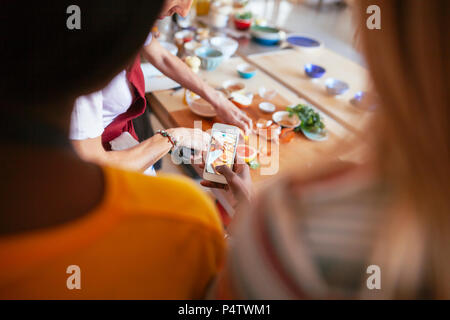 Close-up of woman taking smartphone picture of instructor working in a cooking workshop - Stock Photo