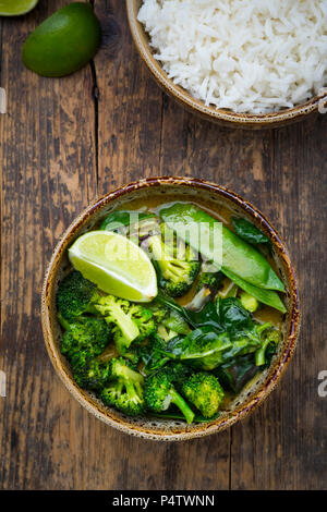 Green thai curry with broccoli, pak choi, snow peas, baby spinach, lime and bowl of rice - Stock Photo