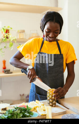 Smiling woman cutting pineapple in kitchen - Stock Photo