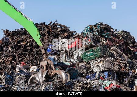 Clamshell grabbing scrap metal of crushed cars - Stock Photo