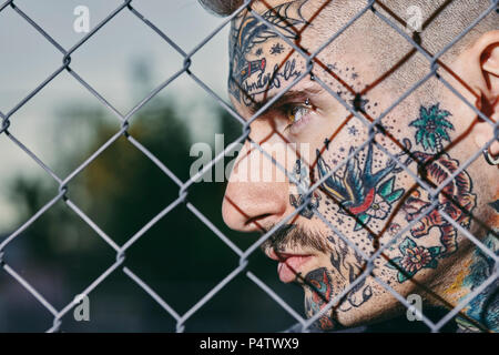 Tattooed face of young man behind fence - Stock Photo