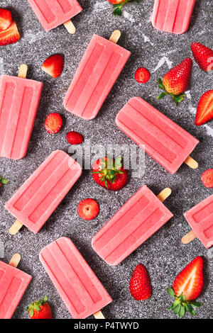 Homemade strawberry ice lollies and strawberries on marble - Stock Photo