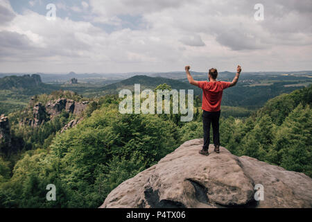 Germany, Saxony, Elbe Sandstone Mountains, man on a hiking trip standing on rock cheering - Stock Photo