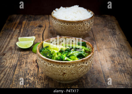 Green thai curry with broccoli, pak choi, snow peas, baby spinach, lime and bowl of rice in the background - Stock Photo