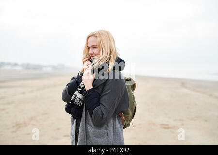 Portrait of blond young woman with backpack on the beach in winter - Stock Photo