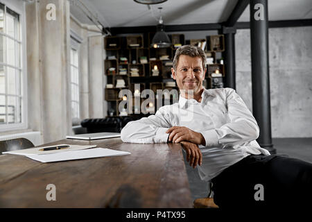 Portrait of mature businessman in loft office - Stock Photo