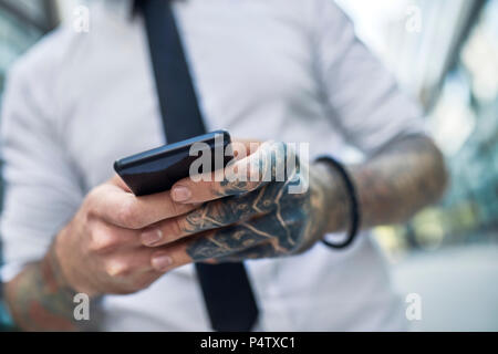 Young businessman with tattooed face using smartphone - Stock Photo