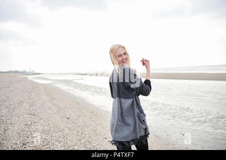 Netherlands, portrait of happy blond young woman  on the beach - Stock Photo