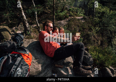 Germany, Saxony, Elbe Sandstone Mountains, friends on a hiking trip having a break taking a selfie - Stock Photo