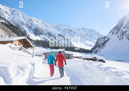 Couple walking in snow-covered landscape - Stock Photo